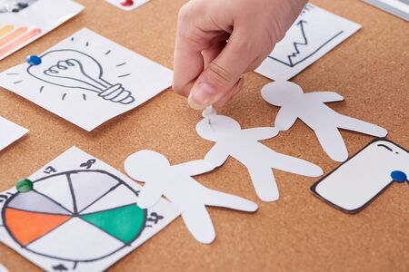 cropped view of woman pinning paper craft decoration on cork board