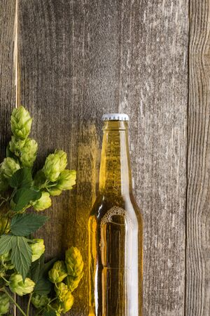 top view of beer in bottle with green hop on wooden surface