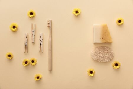 top view of wooden clothespins, toothbrush, natural soap and loofah on beige background with flowers
