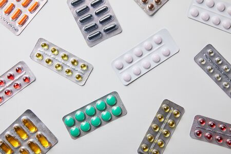 top view of scattered blister packs with different pills isolated in white Фото со стока