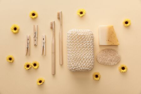 top view of wooden clothespins, toothbrushes, bath sponge, natural soap and loofah on beige background with flowers Stockfoto
