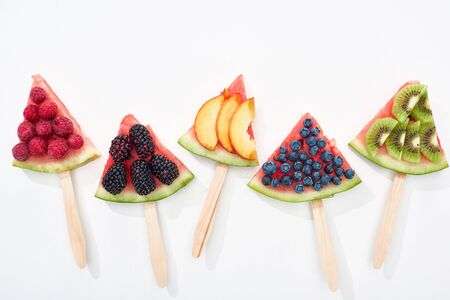top view of delicious watermelon on sticks with seasonal berries and fruits