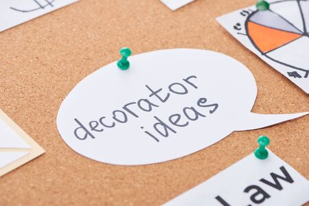 paper card with decorator ideas lettering pinned on cork office board Фото со стока