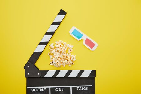 top view of crunchy popcorn near clapper board and 3d glasses on yellow background Stock Photo