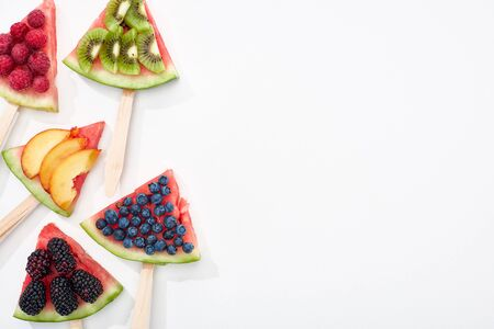 top view of tasty watermelon on sticks with seasonal berries and fruits on white background with copy space 스톡 콘텐츠