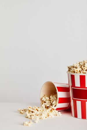 popcorn scattered from red striped paper buckets isolated on grey