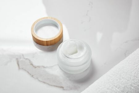 opened jar with cosmetic cream and wooden cap near towel on white surface