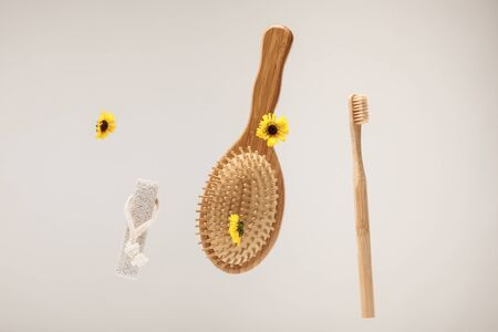 toothbrush, pumice stone, hairbrush and yellow flowers isolated on gray