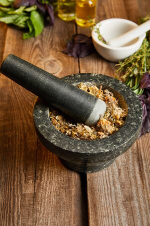 mortars with pestles with herbal mix on wooden surface Stok Fotoğraf