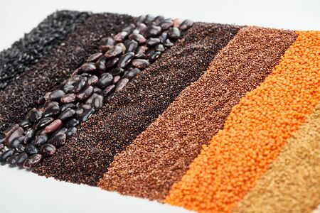 uncooked red lentil, buckwheat, quinoa, black beans and rice isolated on white