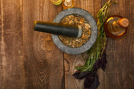 top view of mortar with pestle near fresh herbs and bottles on wooden surface with copy space Stok Fotoğraf