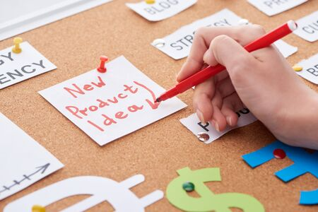 cropped view of woman holding red felt-tip pen near card with new product idea inscription on cork board Stockfoto