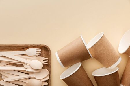 top view of rectangular wooden dish with forks and spoons near paper cups on beige background