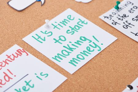 paper card with work motivation message pinned on cork office board