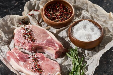 raw pork steaks on parchment paper near wooden bowls with salt and pepper on black marble surface Stok Fotoğraf
