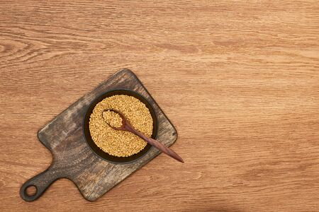 top view of bowls whole grains with spoon on wooden cutting board