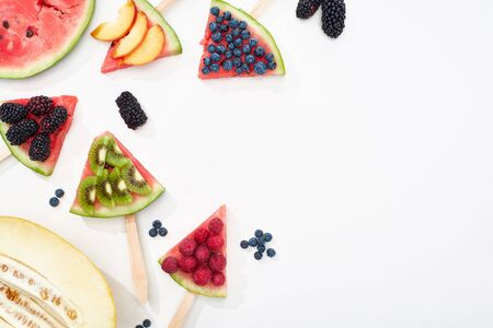 top view of delicious watermelon on sticks with seasonal berries and fruits on white background with copy space 写真素材