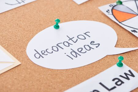 paper card with decorator ideas text pinned on cork office board