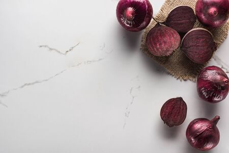 top view of red onions and beetroots on marble surface with hessian