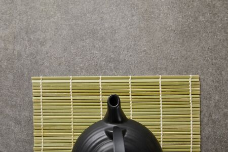 top view of green bamboo table mat with black teapot on grey surface
