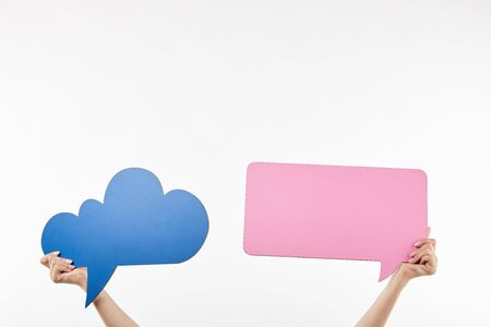 cropped view of woman with blue thought and pink speech bubbles in hands isolated on white Stock Photo