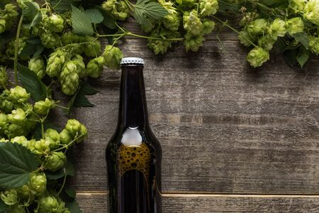 top view of beer in brown bottle with green hop on wooden rustic table Stock Photo