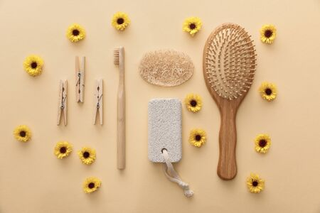 top view of wooden clothespins, toothbrush, hairbrush, pumice stone and loofah on beige background with flowers Stockfoto