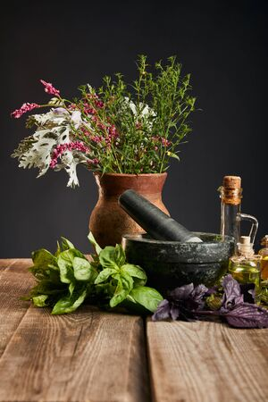 grey mortar near clay vase with fresh and herbs on wooden table isolated on black