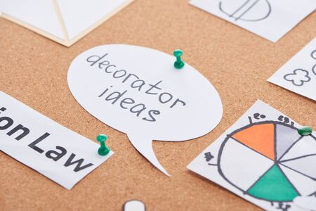 paper cards with diagram and decorator ideas inscription pinned on cork office board