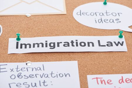 paper cards with decorator ideas and immigration law texts pinned on cork office board Фото со стока