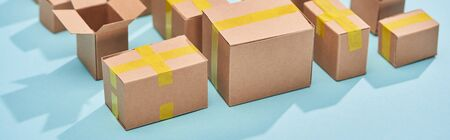 panoramic shot of cardboard postal boxes on blue background