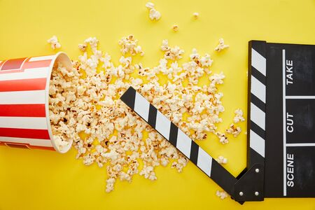 top view of delicious popcorn scattered on yellow background with clapper board