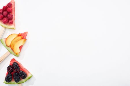 top view of delicious watermelon on sticks with seasonal berries and peach on white background with copy space 写真素材