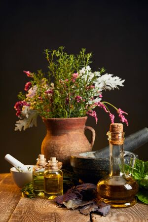 clay vase with fresh herbs and flowers near mortar and pestle and bottles on wooden table