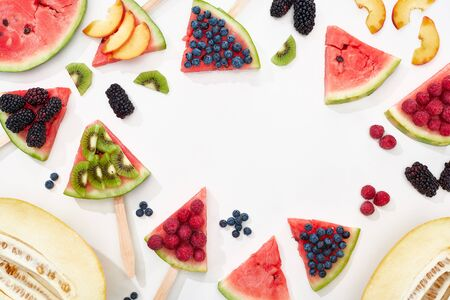 top view of delicious juicy watermelon on sticks with seasonal berries and fruits on white background with copy space
