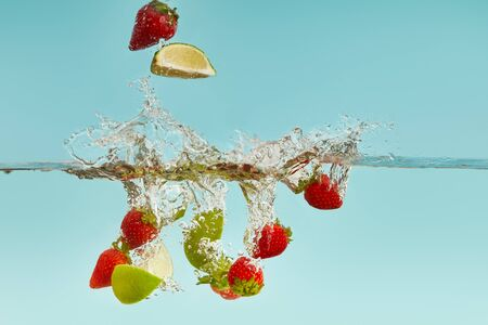 lime pieces and strawberries falling deep in water with splash on blue background