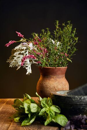 clay vase with fresh wildflowers and herbs on wooden table isolated on black
