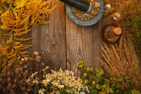 top view of mortar with pestle and bottles near wildflowers and herbs on wooden surface with copy space Фото со стока