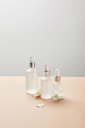 cosmetic glass bottles and few jasmine flowers on beige isolated on grey 版權商用圖片