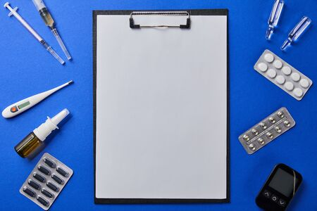 top view of folder with blank paper rounded by various medical supplies on blue surface