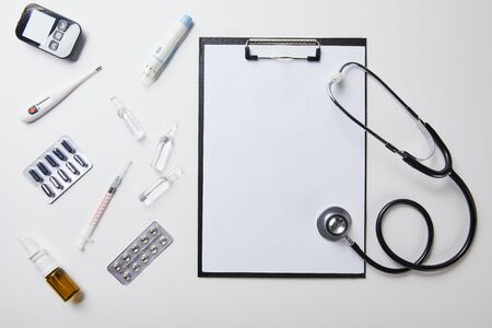top view of various medical supplies near folder with blank paper and stethoscope on white
