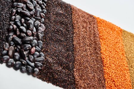 uncooked red lentil, buckwheat, black quinoa and beans seeds isolated on white