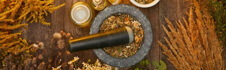 panoramic shot of grey mortar with herbal mix and pestle on wooden table Фото со стока