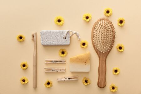 top view of wooden clothespins, toothbrush, hairbrush, pumice stone and piece of soap on beige background with flowers