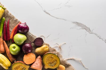 top view of hessian with autumn vegetables on marble surface