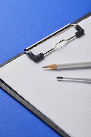 close up view of pencil and thermometer on clipboard isolated on blue