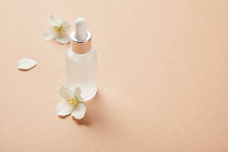 cosmetic glass bottle with serum and few jasmine flowers on beige Imagens