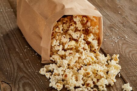 delicious popcorn scattered from paper bag on wooden background