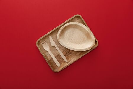 top view of natural rectangular wooden dish with plate, fork and knife on red background Stock fotó