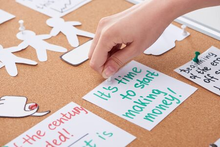 cropped view of woman pinning card with work notes on cork board